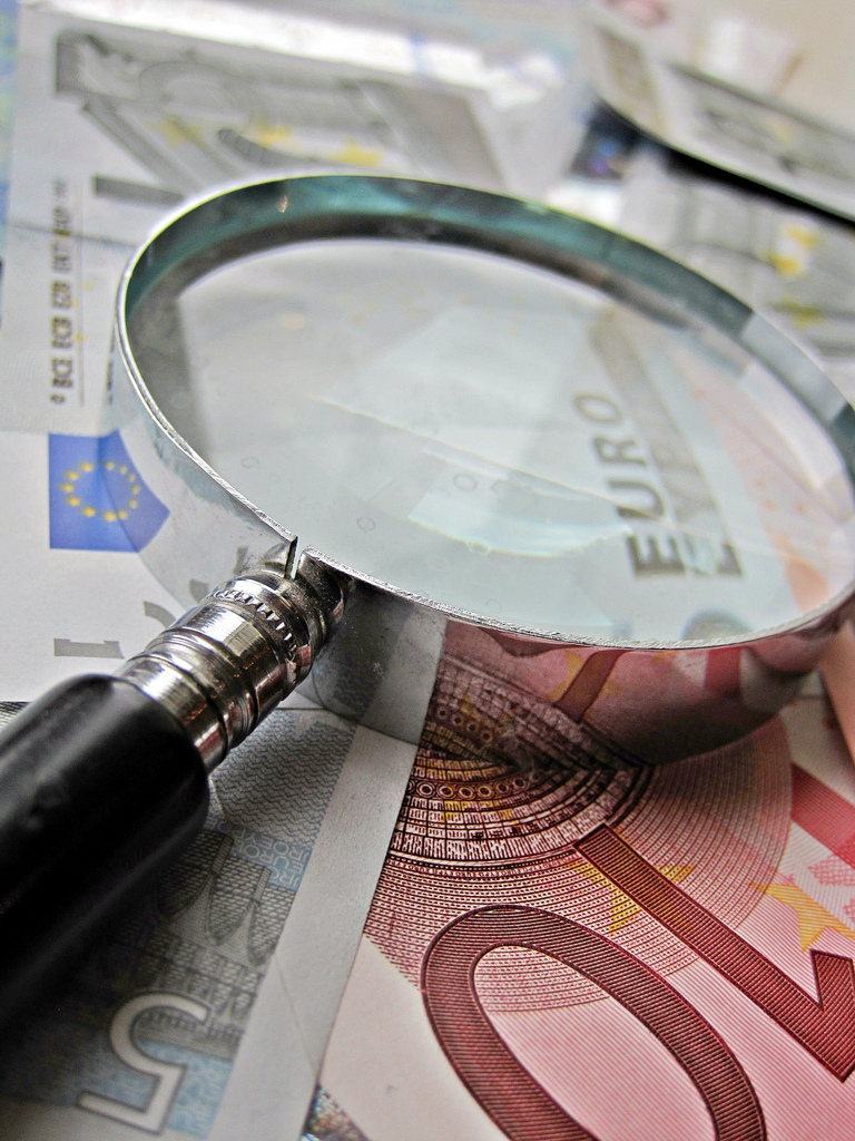 Euros and Magnifying Glass by Images Money